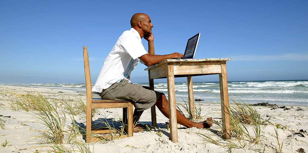 Man working at his desk on the beach