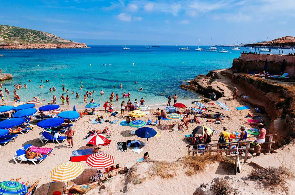Tourists in Cala Compte beach
