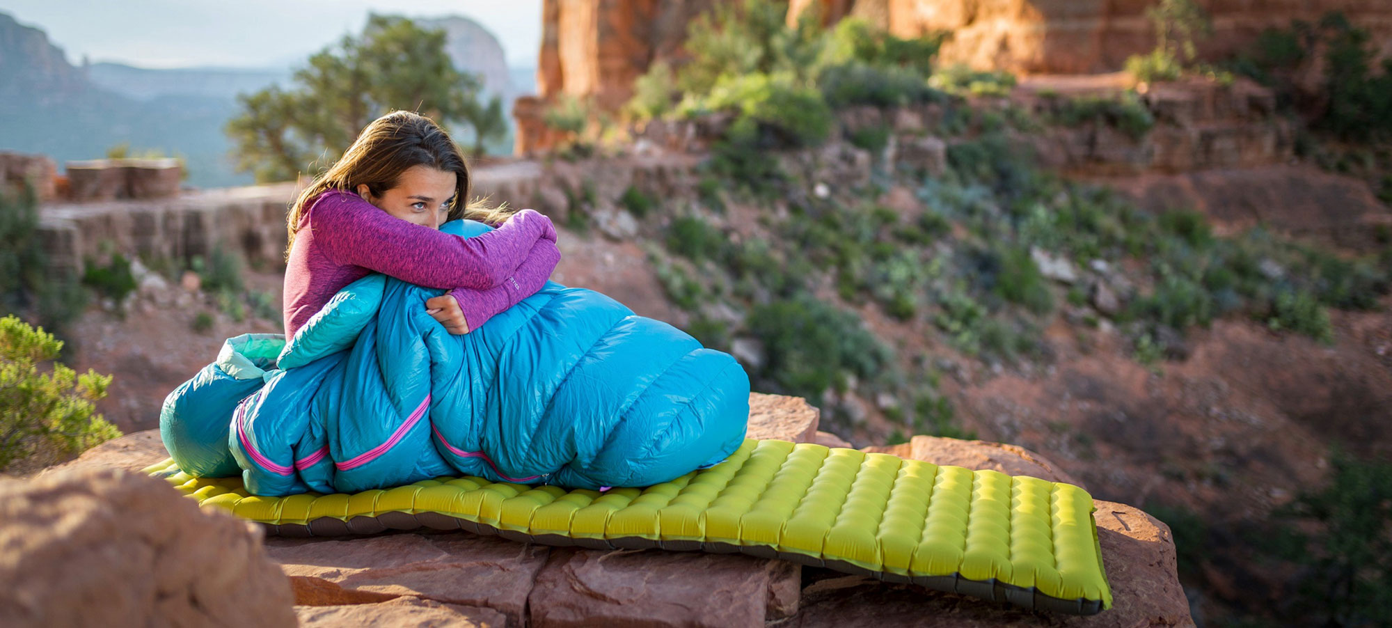 Woman camping in the outdoors, laying on a Nemo Tensor Insulated sleeping pad