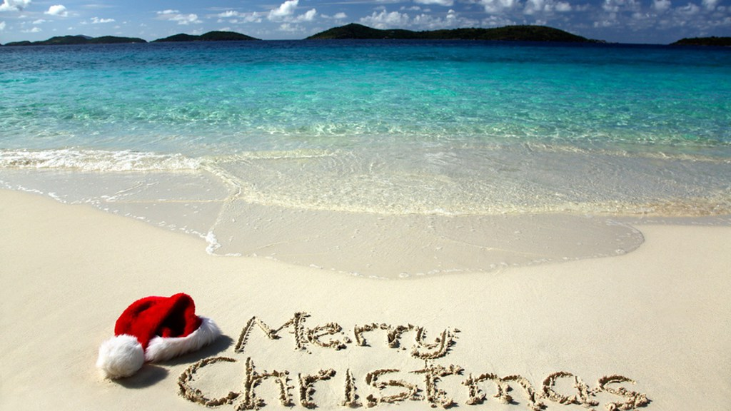 Christmas Hat and a Merry Christmas Written on White Sandy Beach