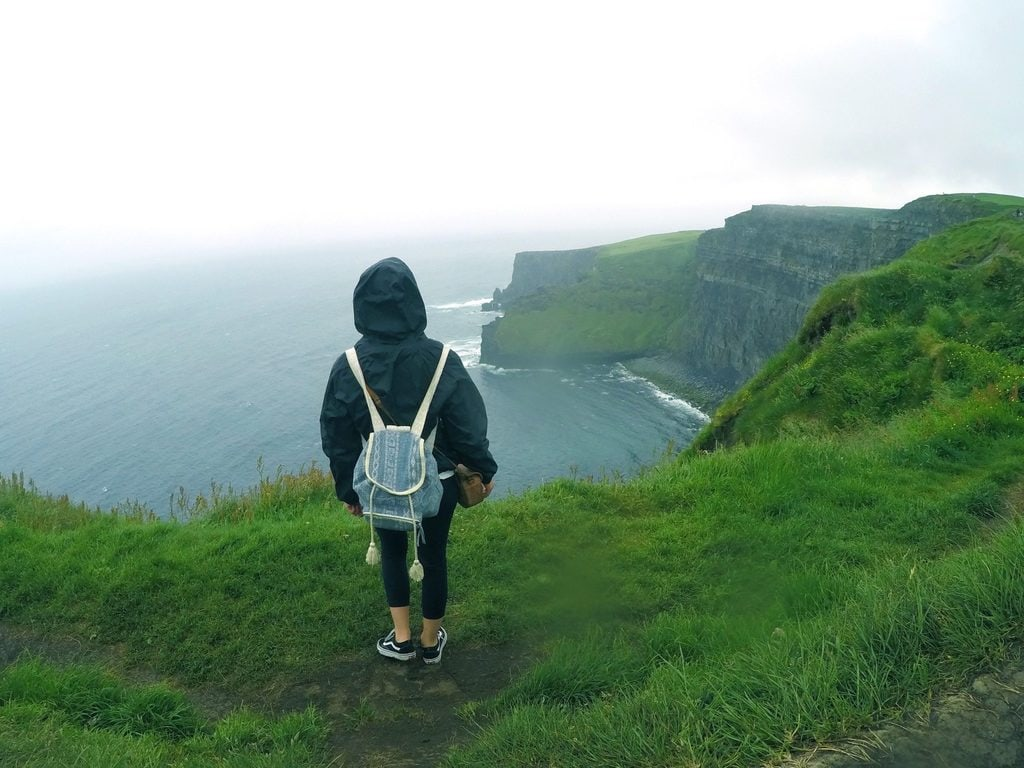 Traveler looking over a sea cliffside