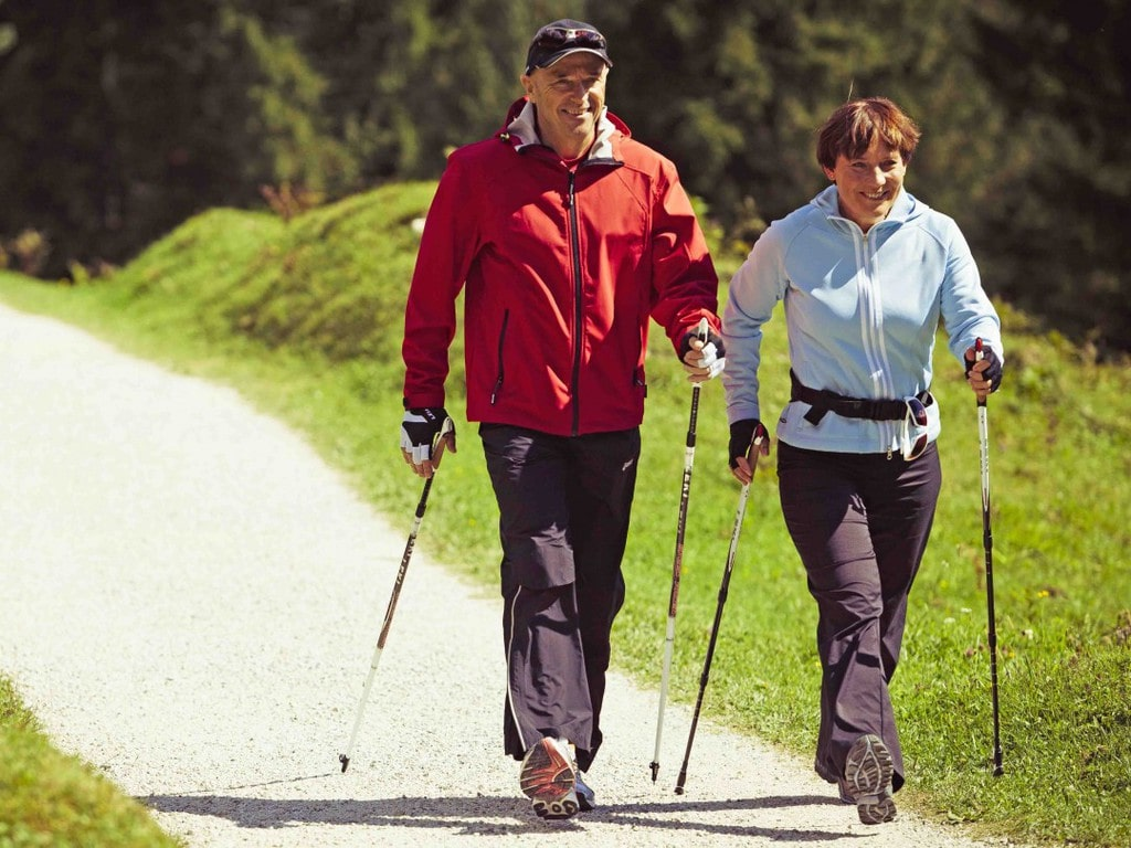 An elderly couple doing Nordic walking