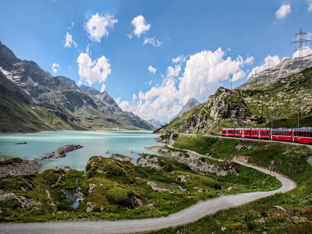 A Swiss train passing by a scenic lake in the majestic Alps
