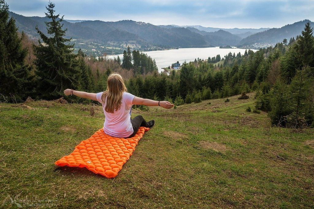 Young woman using a sleeping pad in the outdoors