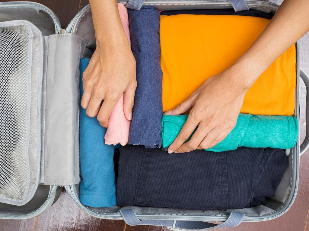 Arranging clothes in a suitcase