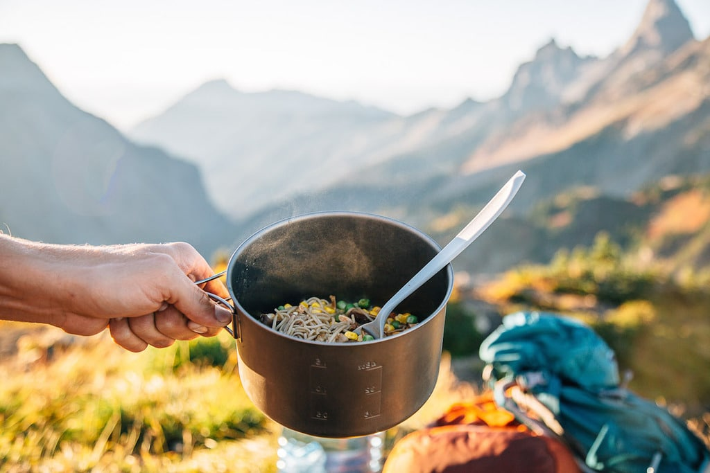 Hand holding a pan of noodles with a backpack and mountain peaks in the background