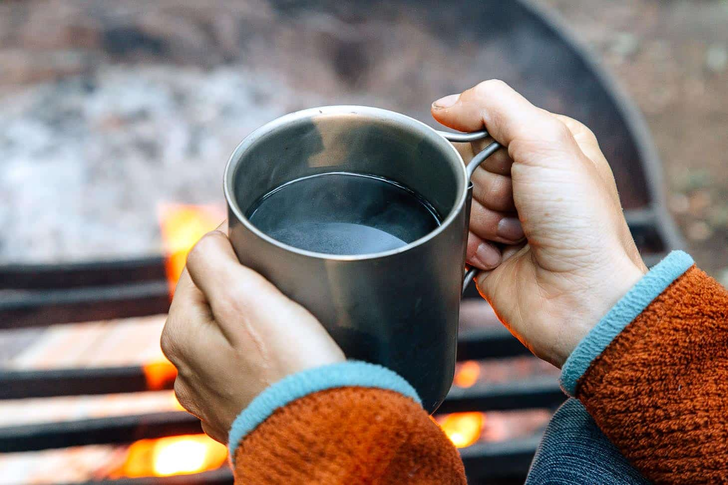 A person holding a can of coffee next to a campfire